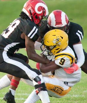 Two Manual defenders bring down Central wide receiver DJure Johnson during the Manual vs Central football game at Manual Stadium.August 20, 2021