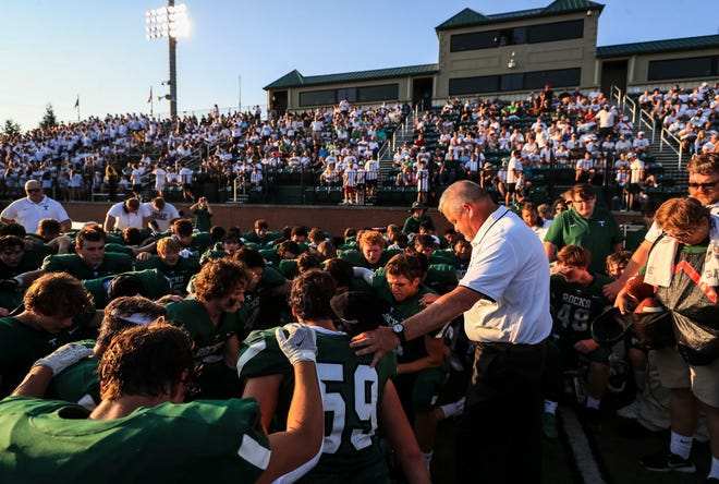 Trinity head football coach Jay Cobb stands at right as his team prays before the game against Carmel Friday night at Marshall Stadium. It was his first game as head coach. The Rocks would lose to the Greyhounds. Aug. 20, 2021