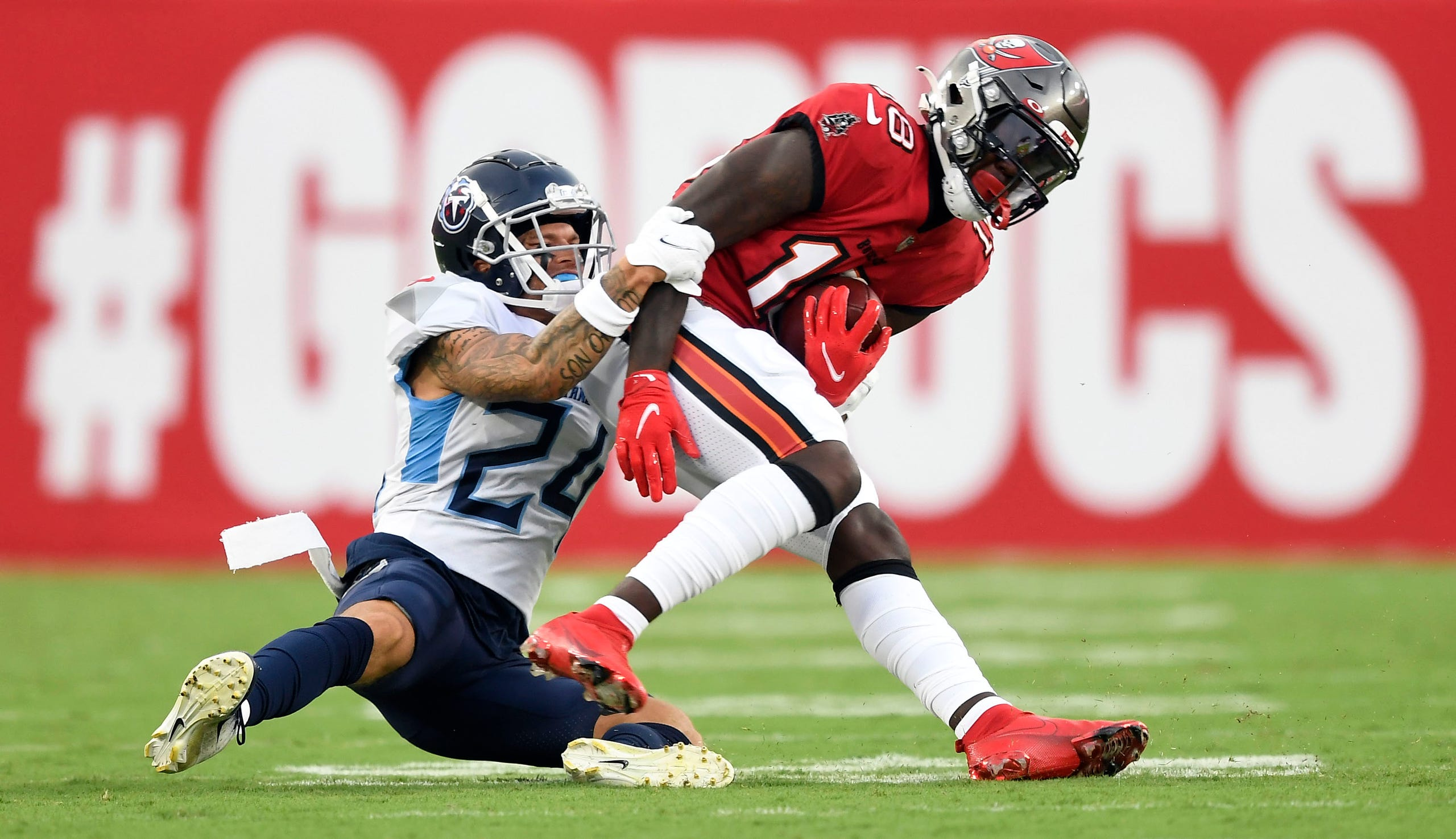 Tennessee Titans cornerback Elijah Molden (24) tackles Tampa Bay Buccaneers wide receiver Tyler Johnson (18) during the first quarter of an NFL preseason game at Raymond James Stadium Saturday, Aug. 21, 2021 in Tampa, Fla.