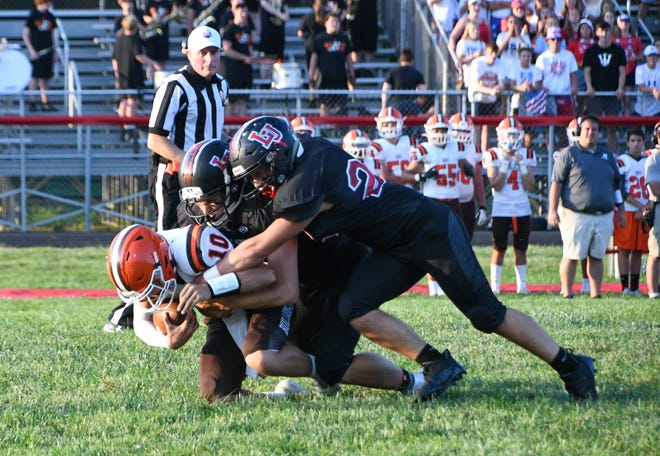 Liberty Union's Kalib Riddle and Austin Ety sack Heath quarterback Brayden Bayles during the first half of the season opener Friday Aug. 20, 2021. The Lions fell 20-13 to the visiting Bulldogs.
