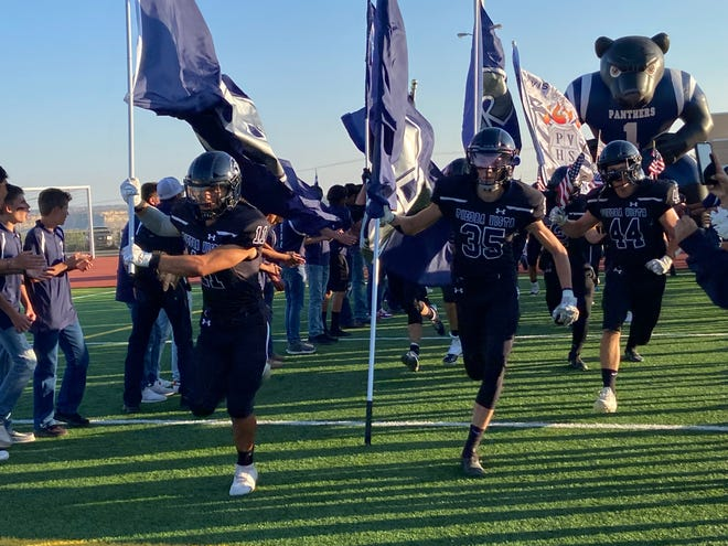 Tatum Etsitty (11), Jack Thompson (35) and Trey Valdez (44) lead the Piedra Vista football player charge onto the field for their home opener against Los Lunas, Friday, August 20 at Hutchison Stadium