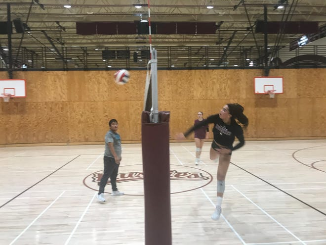Aug. 21, 2021; Hamilton girls volleyball outside hitter Micah Gryniewicz swings down for an attack during the team practice at their school's gymnasium in Chandler, Ariz.