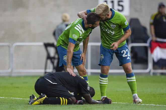 Columbus Crew defender Jonathan Mensah (4) kneels while Seattle Sounders Nicolas Benezet (20) and Kelyn Rowe (22) celebrate the team's 2-1 win at the end of extra time during the game at Lower.com Field on Saturday, Aug. 21.