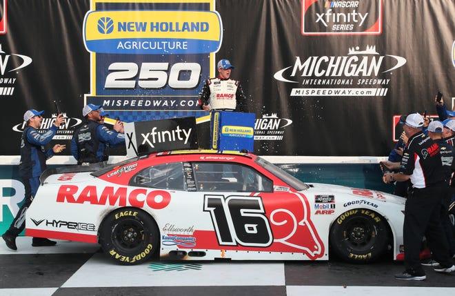 AJ Allmendinger celebrates in victory lane after winning Saturday's New Holland 250 at Michigan International Speedway.