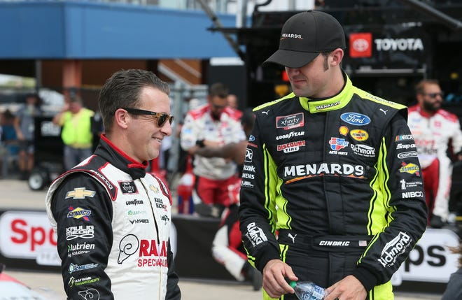 Kaulig Racing's AJ Allmendinger, left, and Team Penske's Austin Cindric, right, talk before Saturday's New Holland 250 at Michigan International Speedway. Cindric has led the points since the opening race of the year, but Allmendinger has closed the gap after winning on Saturday.