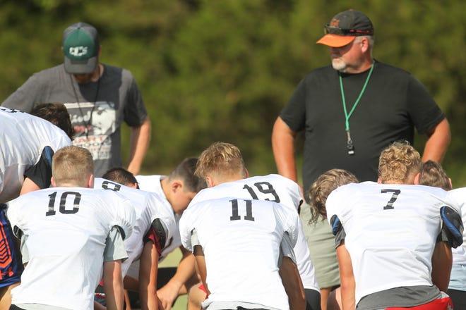 The Central Christian Cougars football team listens to defensive coordinator Matt Barnett (left) and offensive coordinator Mark Barnett (right) following practice at Central Christian School in Hutchinson.