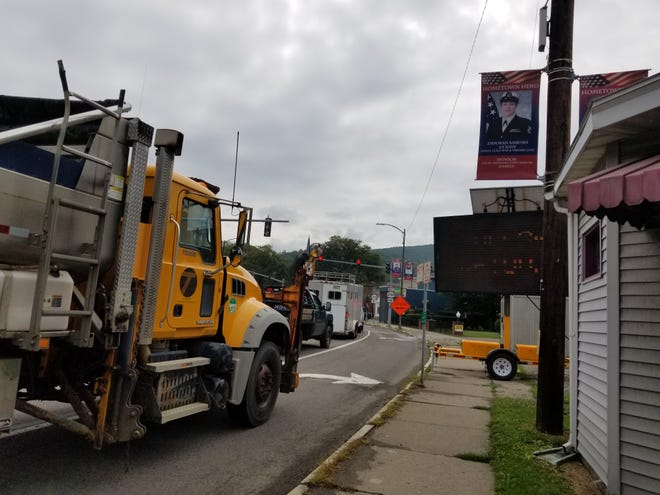 A New York state Department of Transportation truck rumbles through the village of Canisteo, Saturday, Aug. 21, 2021. The DOT truck was one of many work vehicles responding to major road damage following last week's flash floods.