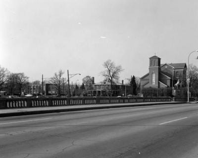 This photo shows the Monroe Street Bridge as viewed toward the northwest, with the St. Mary of the Immaculate Conception Church and Monroe Catholic Central High School in the background.