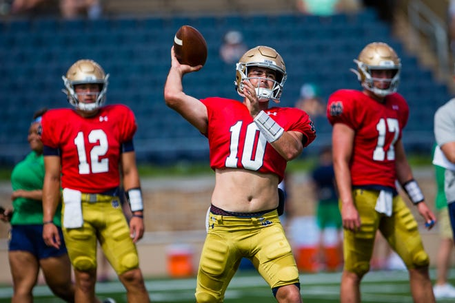 Irish No. 2 QB Drew Pyne (10), flanked by No. 3 Tyler Buchner (12) and starter Jack Coan (17),  runs a drill during football practice Thursday, Aug. 19, 2021 at Notre Dame Stadium.