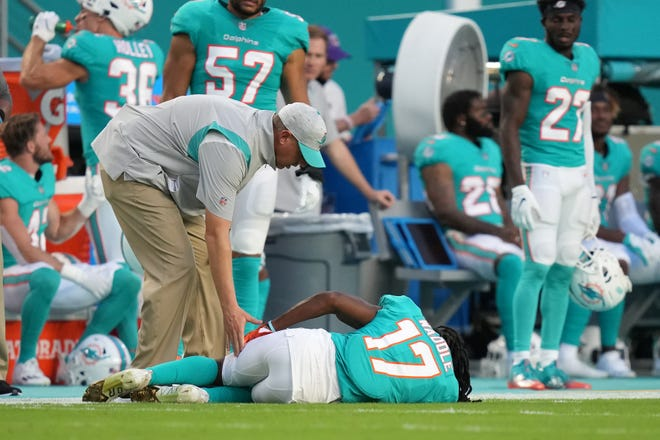 A trainer attends to Dolphins rookie receiver Jaylen Waddle,  who went down with an apparent injury, during the first half of Saturday's preseason game against the Falcons.