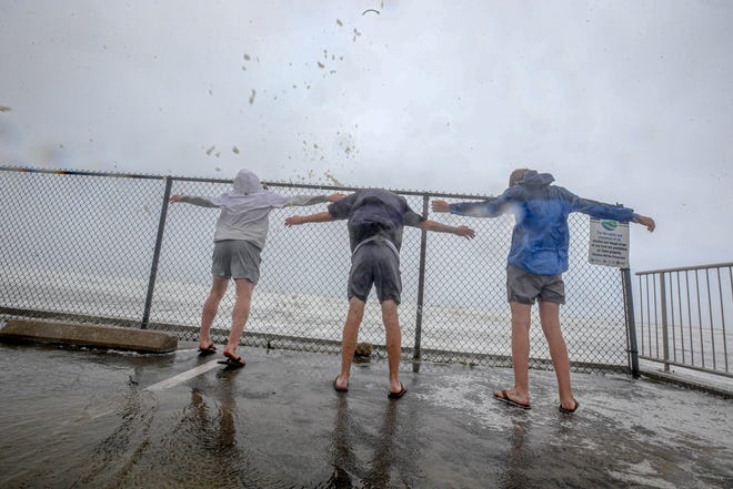 Sightseers brave the wind and rain at Narragansett Beach as Tropical Storm Henri reaches Rhode Island Sunday. The storm brought more than 3 inches of rain to some parts of Rhode Island.