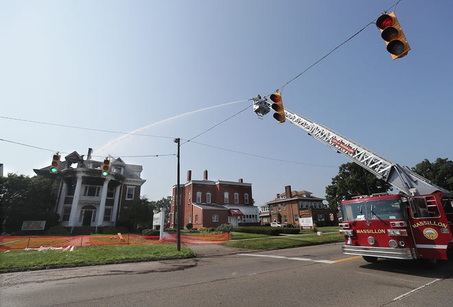 Massillon firefighters shoot water onto the roof of this historic building at 729 Lincoln Way E hoping to douse hot spots Sunday morning.