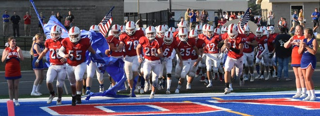 The Patriots charge onto the field for the start of the first game on the new turf field.
