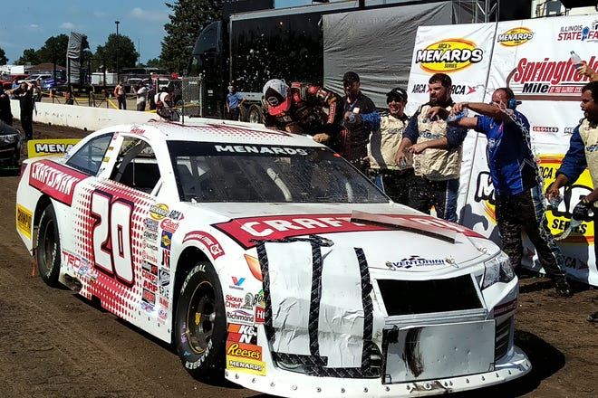Corey Heim climbs out of his car while his teammates douse him in water to celebrate Heim's victory at the USAC Racing Series Allen Crowe 100 on Sunday at the Illinois State Fairground's Springfield Mile.