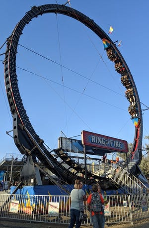 Fairgoers take a ride on the Ring of Fire on the midway Saturday evening at the Brown County Fair.