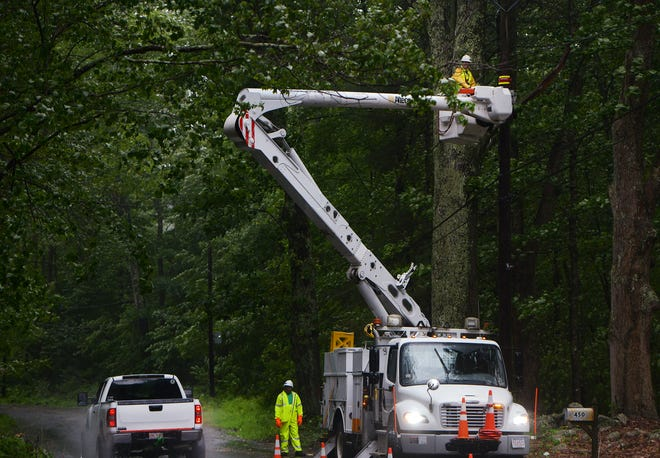 Power lines along Pine Street in Leicester are worked on during the storm Sunday.