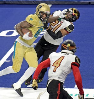 Massachusetts Pirates wide receiver Thomas Owens levels Iowa Barnstormers' Steven Rowzee with a straight arm after a 20-yard reception during Saturday night's Indoor Football League game at the DCU Center.