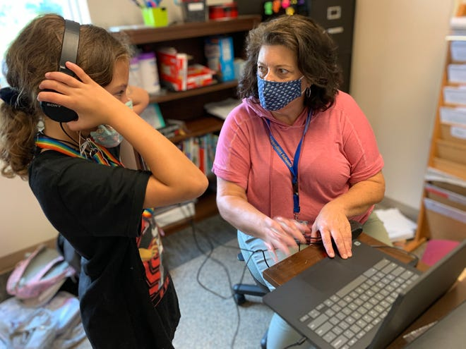 An instructor at Lawrence County Independent Schools plays a sound for a student, who is wearing headphones.