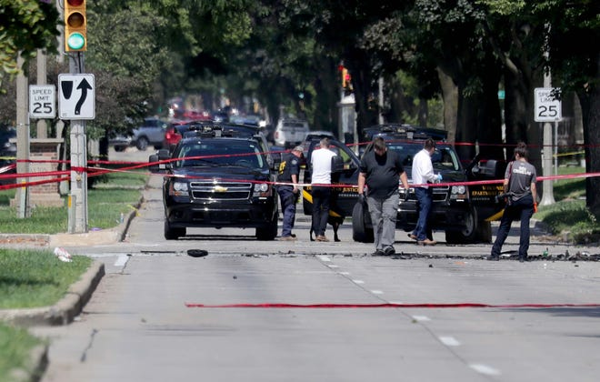Officials investigate the scene of a shooting that left one man dead and a Greenfield police officer in critical condition near South 27th  and West Becher streets in Milwaukee on Sunday.