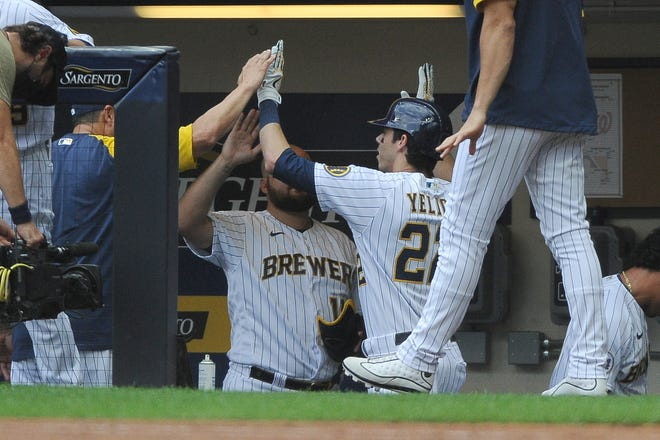 Aug 21, 2021; Milwaukee, Wisconsin, USA;  Milwaukee Brewers first baseman Rowdy Tellez (11) congratulates Milwaukee Brewers left fielder Christian Yelich (22) after hitting a home run against the Washington Nationals in the first inning at American Family Field. Mandatory Credit: Michael McLoone-USA TODAY Sports