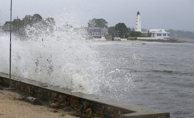 Waves crash against the sea wall near New London Harbor Lighthouse as Tropical Storm Henri approaches Sunday, Aug. 22, 2021, in New London, Conn. (AP Photo/Stew Milne)