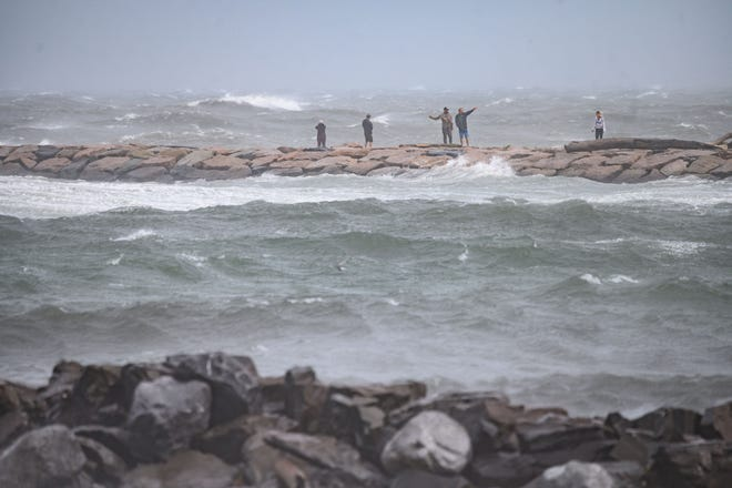 People watch the waves as they stand on a beach as Tropical Storm Henri passes, in Montauk, Long Island on August 22, 2021. - Tropical Storm Henri -- packing strong winds and heavy rain -- made landfall in Rhode Island on the east coast of the United States on Sunday, meteorologists said, with millions in New England and New York's Long Island preparing for flash flooding, violent winds and power outages.The US National Hurricane Center said in its 11:00 am (1500 GMT) advisory that Henri was 15 miles (25 kilometers) southeast of Montauk Point in New York state. (Photo by Ed JONES / AFP) (Photo by ED JONES/AFP via Getty Images) ORG XMIT: 0 ORIG FILE ID: AFP_9LH63R.jpg