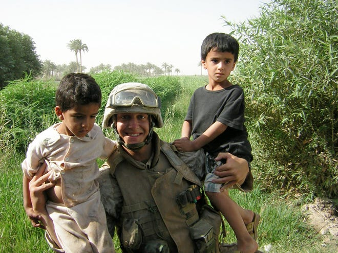Cpl. Joseph A. Tomci, of Stow,  was killed in Iraq Aug. 2, 2006. This picture is of Tomci with two Iraqi children in May 2005.