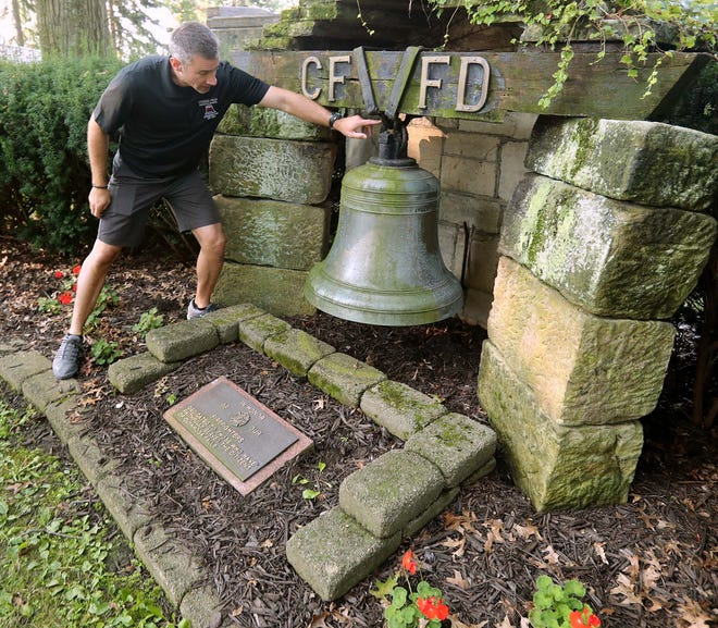 Cuyahoga Falls Fire Department Capt. Matt Kee points to where the historic Cuyahoga Falls Fire Department fire bell was detached from its mount Saturday and moved from Oakwood Cemetery to Fire Station No. 3.