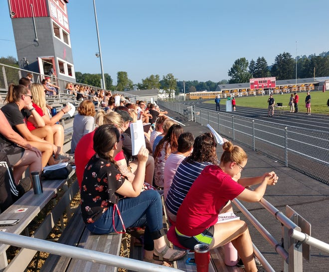 Loudonville-Perrysville School Staff, gathered for a mass teacher in-service Monday morning in Redbird Stadium, listen to Mike Bandy of the L-P Loudonville-Perrysville School staff, gathered for a mass teacher in-service Monday morning in Redbird Stadium, listen to Mike Bandy of the L-P School Foundation announce a $100,000 challenge from the Russell and Mary Ramser family.