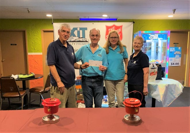 EXIT Realty Premier owner and broker Roger Kopernik (second from left) presented Major John Morrison (left) with a donation of $500 to help stock the shelves of the Cheboygan Salvation Army's food pantry.