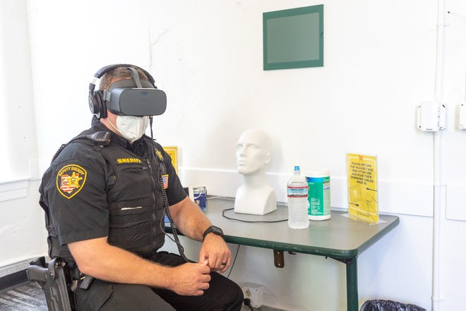 """Deputy Jayson White, of the Athens County Sheriff's office, experiences the """"Chet"""" training scenario at the Appalachian Law Enforcement Initiative event hosted at the Ohio University Police Department on Aug. 21. The specific training simulation that White watched aims to train law enforcement officers to appropriately address someone with mental illness."""