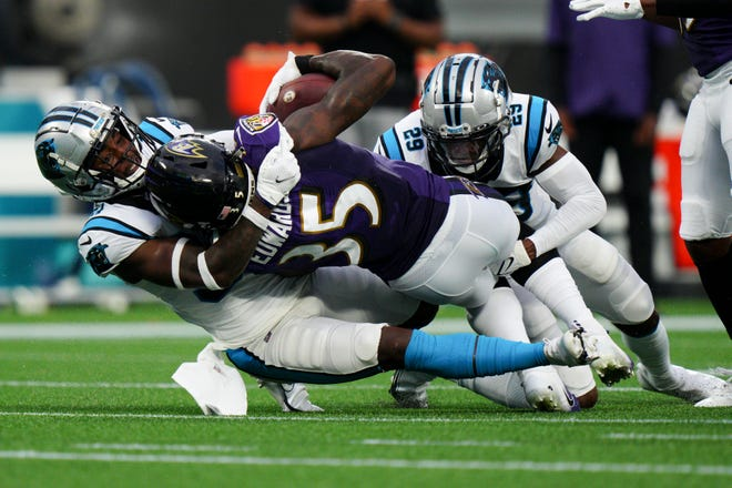 Baltimore Ravens running back Gus Edwards is tackled by Carolina Panthers defensive back Sean Chandler and cornerback Rashaan Melvin (29) during the first half of a preseason NFL football game Saturday, Aug. 21, 2021, in Charlotte, N.C. (AP Photo/Jacob Kupferman)