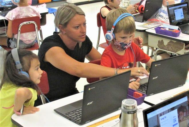 Millersburg Elementary School first grade teacher Keisha Stutzman helps Ben Kaster and Ginnie Roland get logged on to their new Chromebooks.