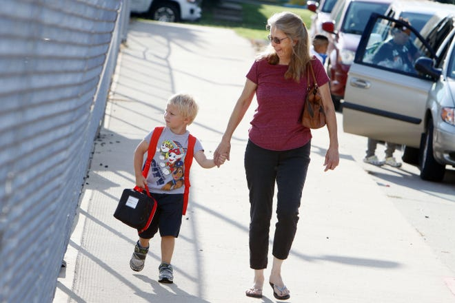 Tricia Boecker walks her grandson, Kaiden Wilson, 5, to his first day of kindergarten Monday as students return to school for the start of the new school year at North Hill Elementary School.