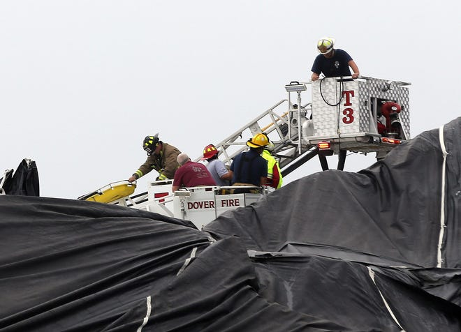 A firefighter grabs onto a stokes basket while working to rescue a worker who fell into a hole in a salt pile on Shattuck Way in Newington Aug. 23, 2021.