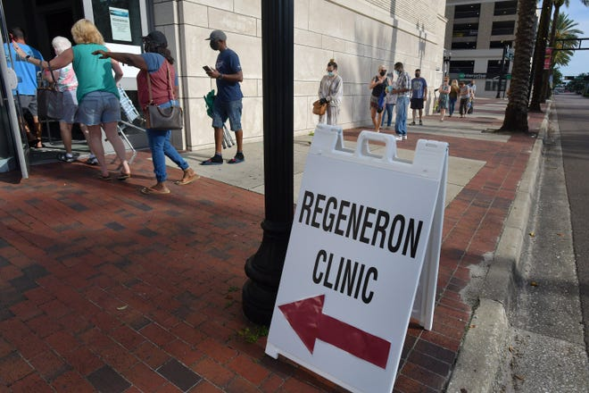Residents make their way down the sidewalk outside the main Jacksonville library after the doors to a Regeneron clinic inside opened Friday morning.
