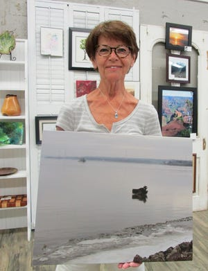 Jodi Haars, president of the Geneseo Art League, holds a piece of photography similar to those that can be entered in the 2021 Maple City Fine Arts Exhibit to be featured in the month of September at the Geneseo Art League Studio and Gallery.