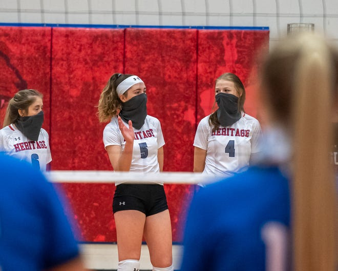 Heritage volleyball players Ashlyn Kerr (6), Harli Elkins (5) and Emilee Casey (4) react on the back row during a volleyball match in the 2020 season.