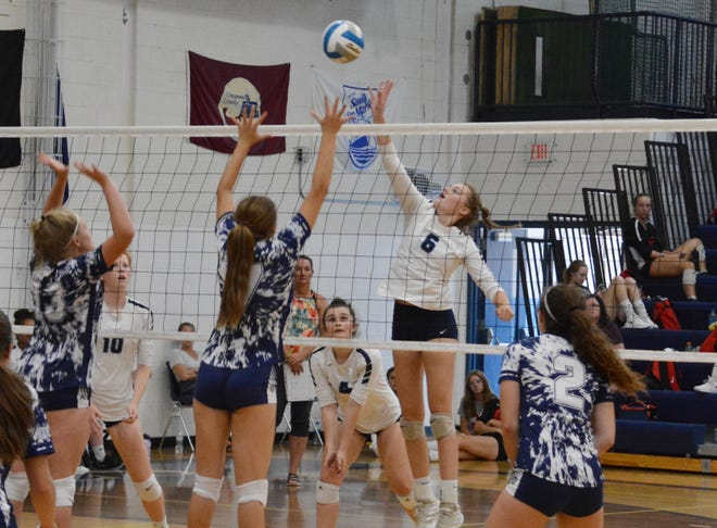 Petoskey's Katelyn Wodek (6) elevates at the net for a tip over a pair of Sault Ste. Marie players Saturday.