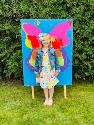 Piper Miller, 6, stands with her butterfly wing painting that was included in this summer's Ottawa Park Summer Exhibit in Cheboygan.