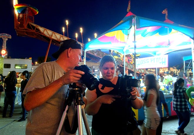 Stockton Camera Club member Stan Sogsti confers with fellow club member Janelle DeRuosi while participating in the club's Carnival Lights workshop June 17, 2011, at the San Joaquin County Fair Stockton.