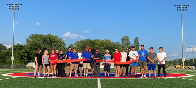 School Board president Chad Cooper and OVHS Athletic Director Brad Greene officially cut the ribbon on the new football field at Owen Valley Friday night. Cooper and Greene were joined by S-OCS Superintendent Andy Cline,  S-OCS Board members, OVHS principal Robert Boltinghouse, OVHS football and soccer coaches, as well as girls and boys soccer players and band members.