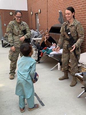 Spc. Julie Bailey. left, and Sgt. Breanna Jessop, right, with the 82nd Airborne Division, play catch with an Afghan child Friday, Aug. 20, 2021, at Hamid Karzai International Airport in Afghanistan. Back on the homefront, Fort Bragg and Fayetteville area organizations are supporting military families of deployed soldiers.