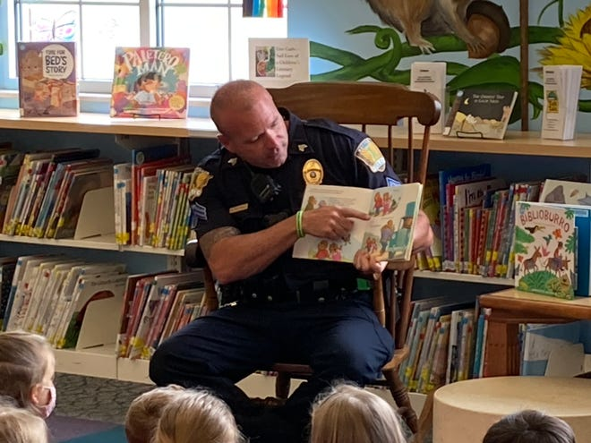 """Sgt. MacNeal reads """"The Berenstain Bears Learn About Strangers"""" with preschoolers at Macedon Public Library. He then shared safety tips and talked about fire safety, since he also serves as a firefighter."""