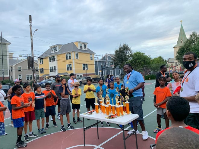 Players in the Davonte Neal Instructional League gather around as Kessen Green (blue shirt) and Vlad Pierre (right) prepare to hand out awards at a ceremony held Aug. 18 at Sennott Park.