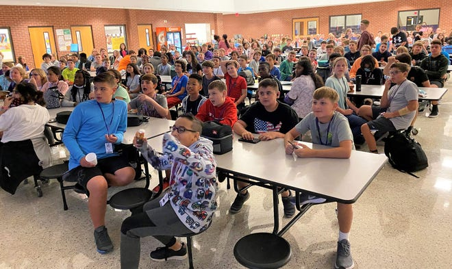 Wylie West Junior High students, finished with lunch, watch Wylie Little League player introductions before the Texas vs. Michigan game began Monday. Play had just started when the students were dismissed but Wylie took a 2-0 lead before a rain delay.