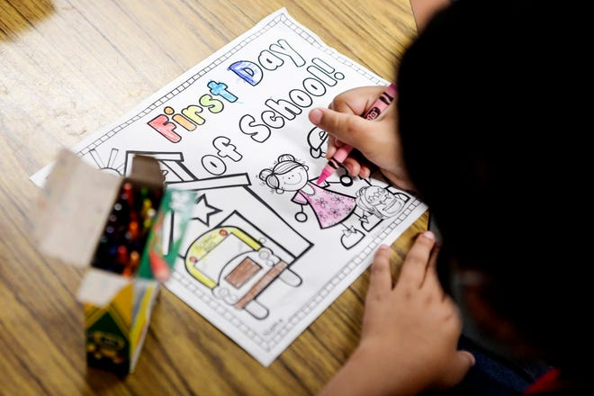 """Weaverville Primary students color papers reading """"Welcome to first grade"""" on their first day of school, August 23, 2021."""