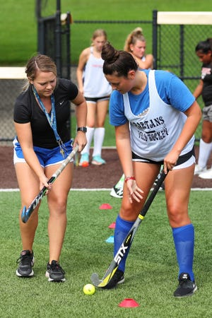 First-year Maine-Endwell field hockey coach Mckenzie Townsend, left, shows Alison Zaverton the proper stick technique during the opening day of practice, Monday, Aug. 23, 2021.
