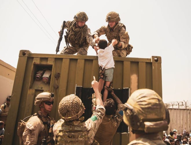 Military personnel lift a child on Aug. 20 during an evacuation at Hamid Karzai International Airport in Kabul, Afghanistan.