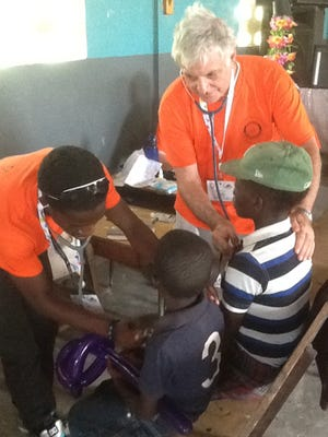 Dr. Robert Lerer examines a child during a mission trip to Haiti.